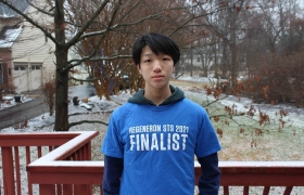 Timothy Qian wearing a blue Regrneron STS 2021 Finalist shirt while on a porch standing in front of a snowy yard.